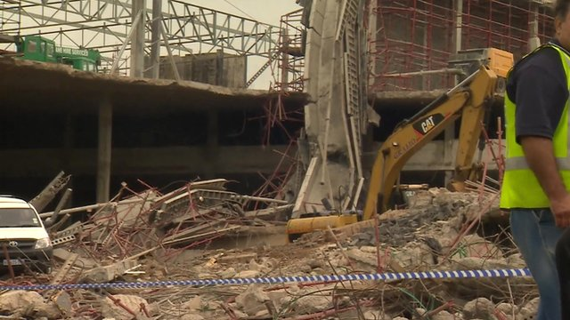 Digger at site of collapsed mall