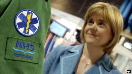 Nicola Sturgeon looking talking to someone from the NHS in Scotland