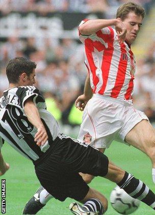 Aaron Hughes tackles Kevin Kilbane