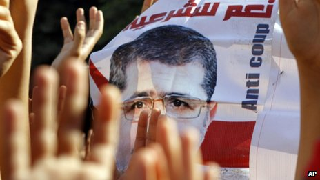 Supporters of Egypt's ousted President Mohammed Morsi raise his poster and their hands with four raised fingers during a protest in Cairo Friday, Nov 15, 2013.