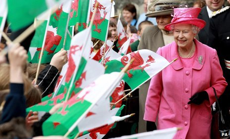 The Queen walks past a crowd of people holding Wales flags