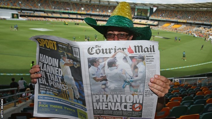 A fan reads the Courier Mail