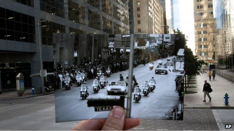 A 21 November 1963 photo of John F Kennedy's motorcade is held up over a 7 November street scene in Houston, Texas