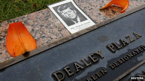 A photo of Kennedy with flowers on a plaque at Dealey Plaza in Dallas, Texas