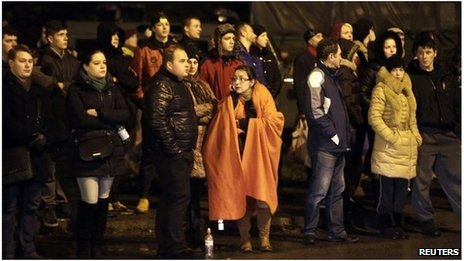 People wait at scene of collapse in Riga, Latvia (21 Nov 2013)