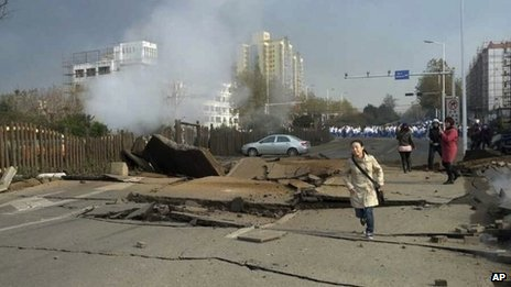 A woman runs near a damaged street following the pipeline explosion in Qingdao