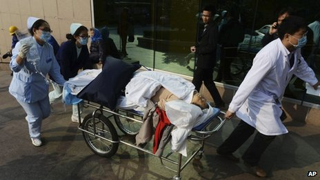A doctor and nurses carry an injured person in a stretcher to a hospital following a pipeline explosion in Qingdao in east China's Shandong province, 22 November 2013