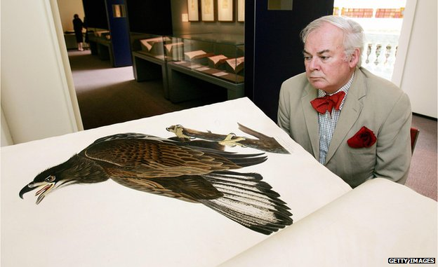 International art critic Patrick McCaughey inspects a print of a White-Headed Eagle in John James Audubon's 'Birds of America' from 1821
