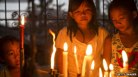Children gather round candles during a Latin mass ceremony at a local Chapel in Santa Rita township on November 22, 2013 in Eastern Samar, Philippines