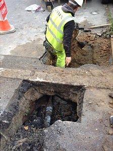 Worker in hole in Trinity Road