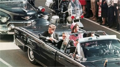 John F Kennedy's motorcade travels through Dallas