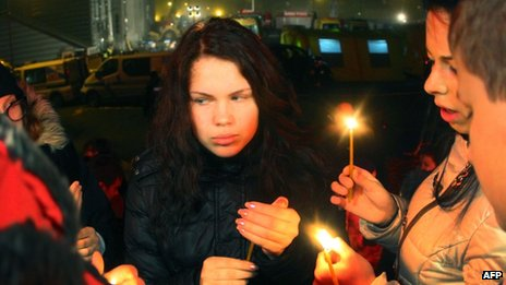 People carry a candles at the scene of the disaster