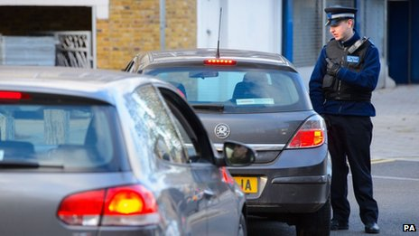 A PCSO speaks to a driver near flats in Brixton, south London, as police are conducting house-to-house inquires in Brixton