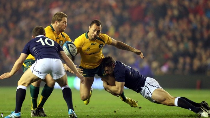 Australia's Quade Cooper, centre is tackled by Scotland's Sean Maitland, right, and Duncan Weir