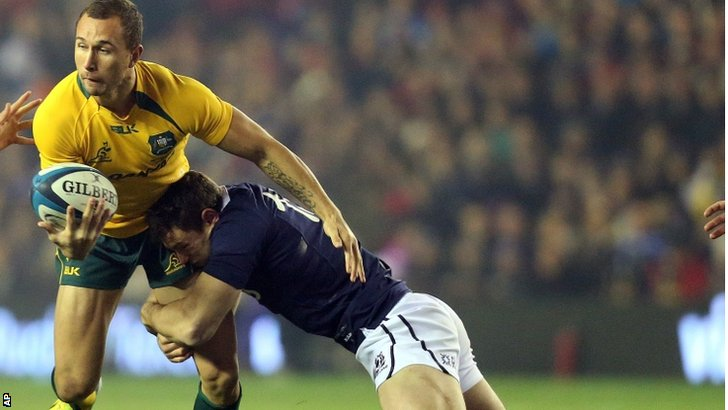 Australia's Quade Cooper, left, is tackled by Scotland's Sean Maitland