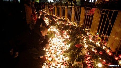 People light candles at the scene of the supermarket collapse in Riga on 23 November 2013