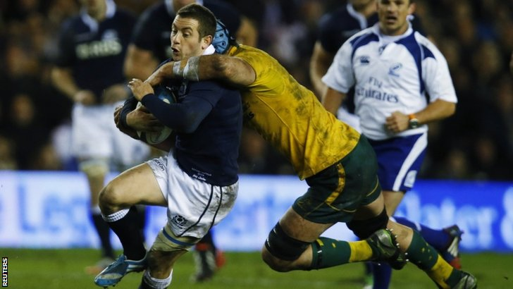 Australia's James Horwill tackles Scotland's Greig Laidlaw (left)