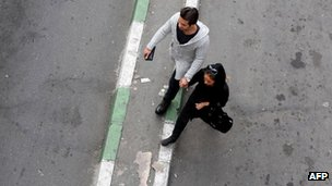 An Iranian couple crosses a street in the capital Tehran on November 24