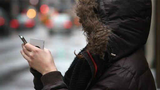 Woman in hooded coat looking at phone