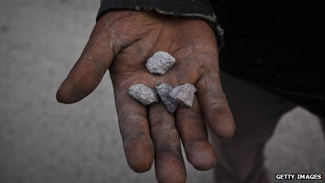 A man holds rocks from eruption of mount Sinabung at Sukanalu village on 24 November 2013 in Karo district, North Sumatra, Indonesia