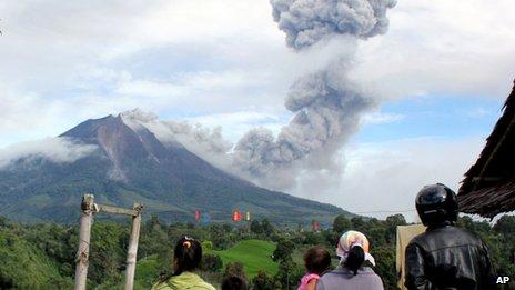 Villagers watch as Mount Sinabung sinabung spews volcanic material in Karo, North Sumatra, Indonesia, 24 November 2013