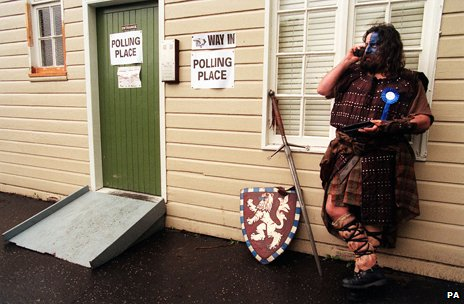 A man dressed as William Wallace leans against a voting booth on his mobile phone