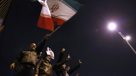 Iranians wave their national flag as they hold a poster of President Hassan Rouhani to welcome Iranian nuclear negotiators upon their arrival from Geneva in Tehran on 24 November 2013 (released by the Iranian Students News Agency, Isna)