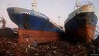 Typhoon survivors walk past ships washed ashore in Tacloban