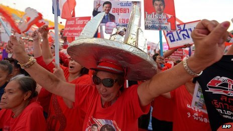 "Thai pro-government ""Red Shirts"" waves clappers as they gather at Rajamangala stadium in Bangkok on 24 November 2013"