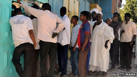Men wait outside a bakery in Khartoum
