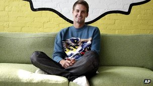Evan Spiegel sits under the Snapchat logo