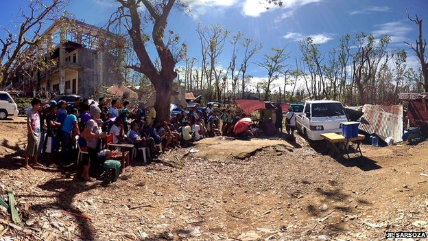 Residents of Estancia town on Panay Island, central Philippines gather around a TV set powered by a battery from a vehicle to watch the Pacquiao-Rios fight last Sunday. Beside them is their roofless Northern Iloilo Polytechnic State College. Photo: JP Sarsoza