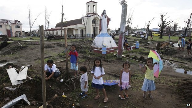 Children stood among ruins in the Philippines