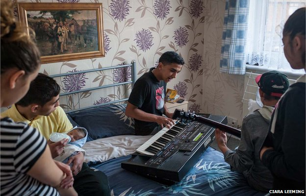 Family members gather to hear Jiri, 19, (centre) play music with a friend