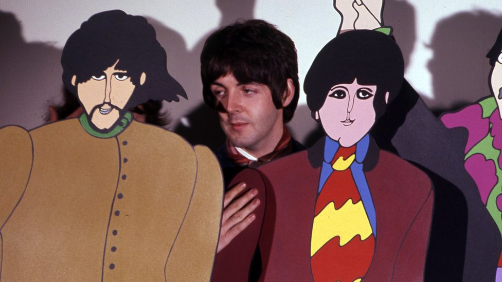Paul McCartney with cardboard cut-outs of The Beatles