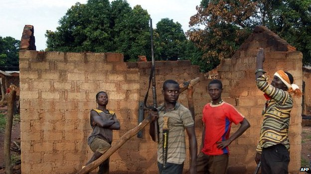 Young people patrol with rifles near a house destroyed by fire on 11 October 2013 in Bogangolo, CAR