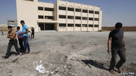 Syrians inspect the aftermath of an air strike on a secondary school in Raqqa (29 September 2013)