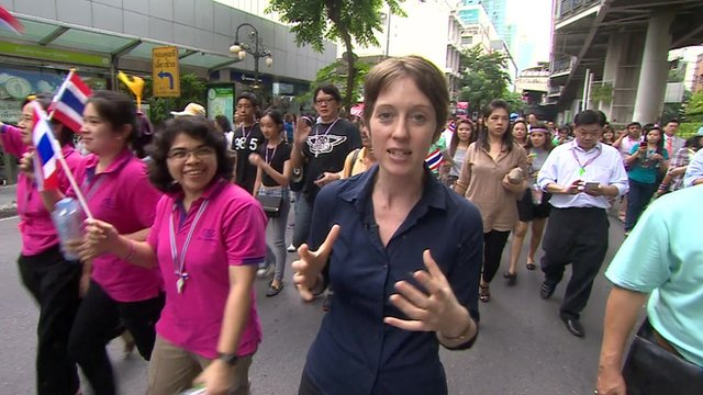 The BBC's Lucy Williamson walks amongst a protest in Bangkok