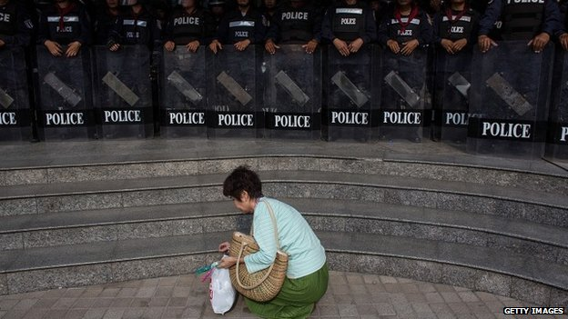 Woman collects rubbish outside Ministry of Culture as riot police look on - 27 November