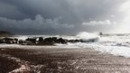 A choppy sea coming ashore on a pebble beach. Grey clouds and a headland in the distance.