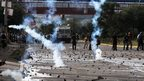 Tear gas is thrown during clashes between police and protesters in Tegucigalpa, Honduras, on 26 November 2013