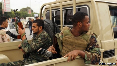 Libyan army soldiers sit in the back of a pick-up truck