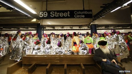 Performers in the 87th Macy's Thanksgiving Day Parade wait for a subway to take them to the start of the parade in New York on 28 November 2013