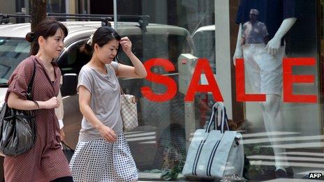 Women walk past a sale sign in Japan