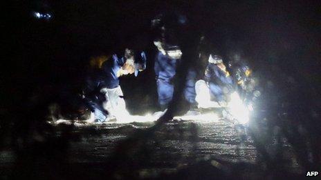 Police investigators inspect a field near Yokota US air base at Tachikawa, west of Tokyo, on 29 November 2013