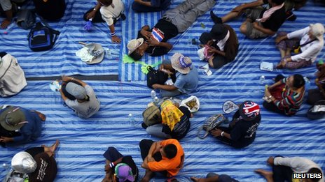 An anti-government protester sleeps among others sitting on the road outside the national police headquarters where they are protesting in Bangkok on 28 November 2013