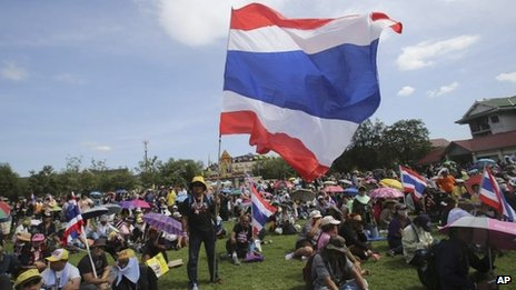 Anti-government protesters with Thai national flags sit at the Royal Thai Army compound in Bangkok, Thailand, 29 November 2013