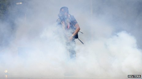 An anti-government protester throws back a tear gas canister at Thai riot police as they attack Government House in Bangkok, 1 December 2013