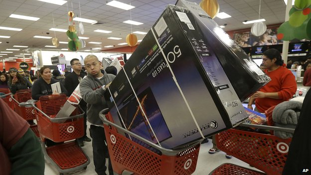 A man pushes two televisions in a shopping cart at a Target store in Colma, Calif., on Thanksgiving Day, Thursday, Nov. 28, 2013.