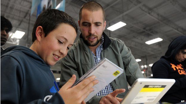 Sabastian Valenzuela, left, and his older brother Alberto compare prices for iPad tablets at a Best Buy late in the evening on Thanksgiving Day, Thursday, Nov. 28, 2013, in Dunwoody, Ga